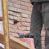 MORE DAMAGED BRICK ARE IN THE PROCESS OF BEING CUT OUT.