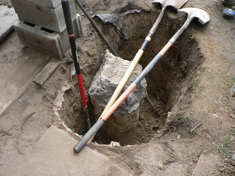 HOLE IS DUG OUT TO ACCOMMODATE LARGER SIZE FOOTING.