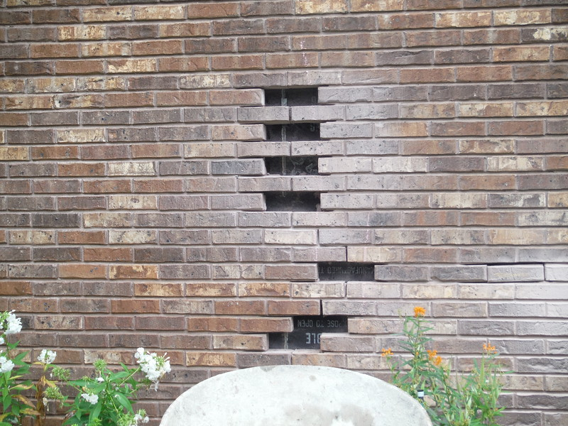 Cracked brick are removed from wall.