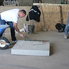 """FOR DEMONSTRATION THIS FIREPLACE IS BEING BUILT ON A PORTABLE FOOTING SO FIREPLACE CAN BE MOVED WITH A FORK LIFT. ON A NORMAL JOB THESE FIREPLACES ARE BUILT ON A 42"""" CONCRETE FOUNDATION. BRICKLAYER SPREADS THE MORTAR TO BEGIN SETTING THE FIRST PIECE."""