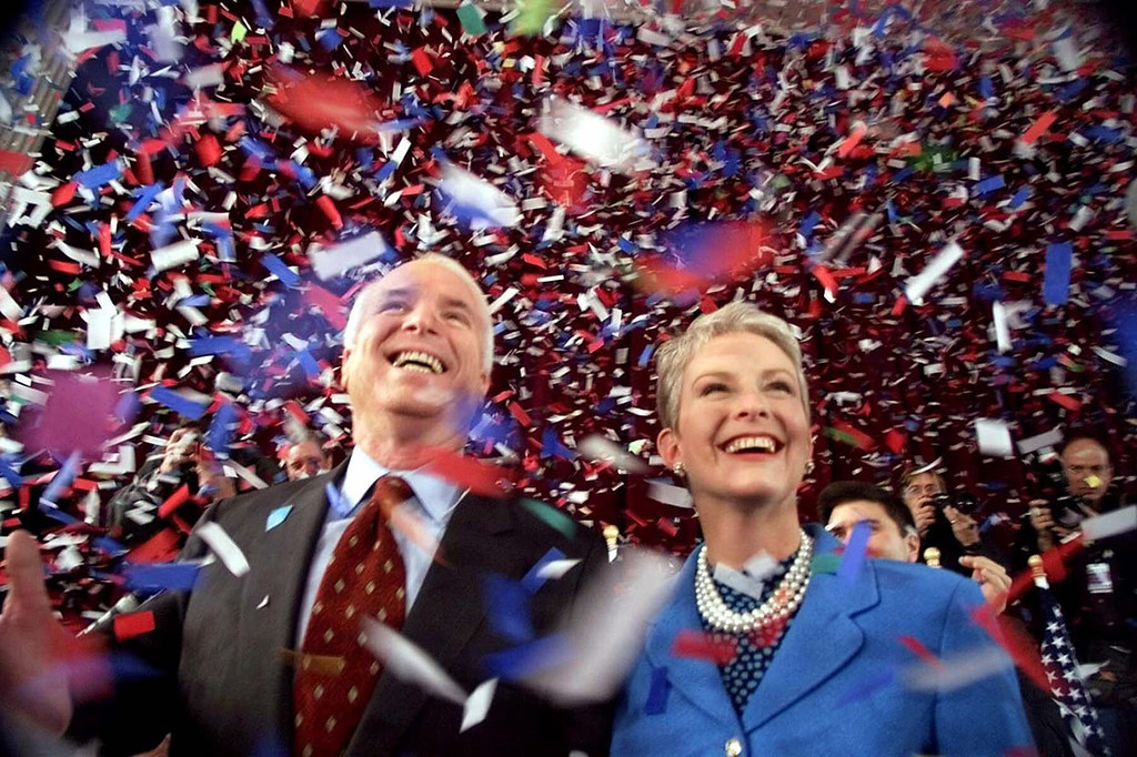 . FILE - In this Jan. 30, 2000, file photo, confetti falls on Republican presidential hopeful Sen. John McCain, R-Ariz., and his wife, Cindy, at the end of their 114th New Hampshire town hall meeting with voters at the Peterborough Town House in Peterborough, N.H. Aide says senator, war hero and GOP presidential candidate McCain died Saturday, Aug. 25, 2018. He was 81. (AP Photo/Stephan Savoia, File)