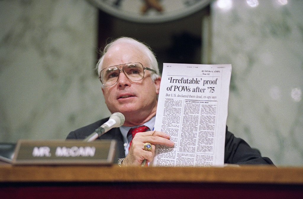 . FILE - In this June 24, 1992, file photo, Sen. John McCain, R-Ariz., holds up an article from the Washington Times during a hearing of the Senate Select Committee on POW/MIA Affairs on Capitol Hill in Washington. Arizona Sen. McCain, the war hero who became the GOP\'s standard-bearer in the 2008 election, has died. He was 81. His office says McCain died Saturday, Aug. 25, 2018. He had battled brain cancer. (AP Photo/John Duricka, File)
