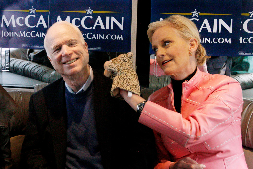 """. FILE - In this Jan. 19, 2008, file photo, Cindy McCain, wife of Republican presidential hopeful Sen. John McCain, R-Ariz., uses a cheetah hand puppet to make her husband laugh as they ride the \""""Straight Talk Express\"""" campaign bus to a polling station in Charleston, S.C., on the day of South Carolina\'s Republican presidential primary. Arizona Sen. McCain, the war hero who became the GOP\'s standard-bearer in the 2008 election, has died. He was 81. His office says McCain died Saturday, Aug. 25, 2018. He had battled brain cancer. (AP Photo/Charles Dharapak, File)"""