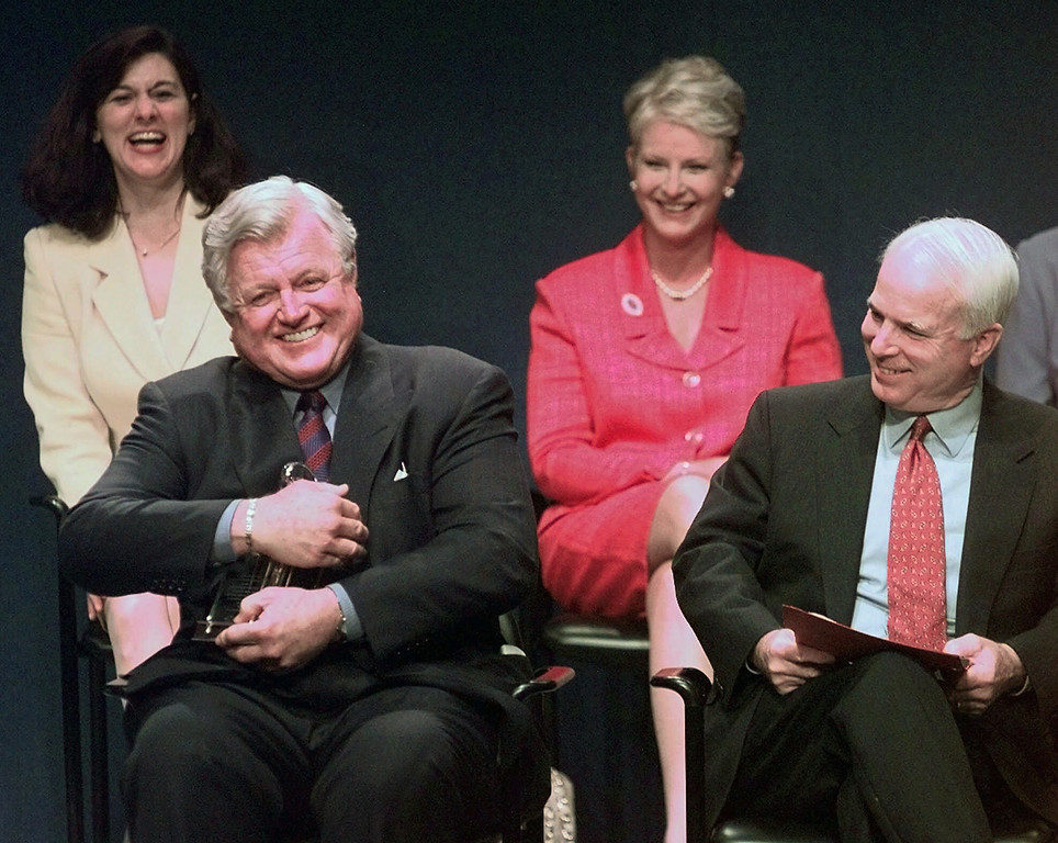 . FILE - In this May 24, 1999, file photo, Sen. Edward Kennedy, D-Mass., jokingly holds the Profile in Courage award as if he intends to keep it, as co-winner, Sen. John McCain, R-Ariz., looks on at right during a ceremony at the John F. Kennedy Library in Boston. In back row are their spouses, Victoria Kennedy, left, and Cindy McCain. Arizona Sen. McCain, the war hero who became the GOP\'s standard-bearer in the 2008 election, has died. He was 81. His office says McCain died Saturday, Aug. 25, 2018. He had battled brain cancer. (AP Photo/Elise Amendola, File)