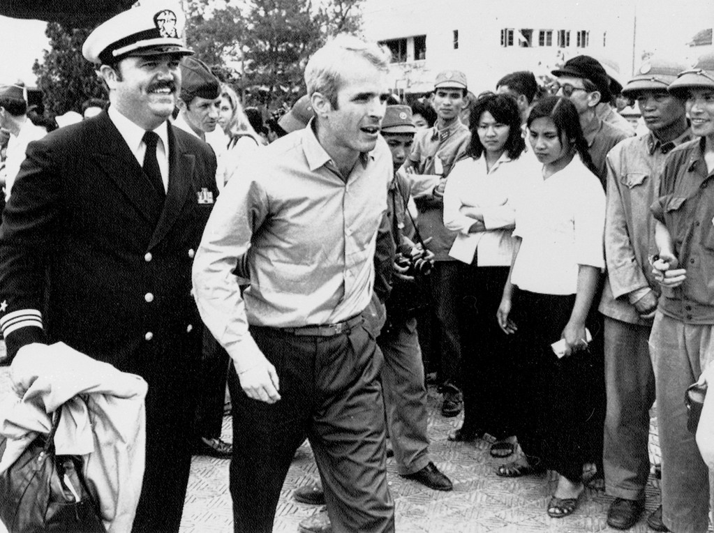 . FILE - In this March 14, 1973, file photo, U.S. Navy Lt. Cmdr. John McCain, center, is escorted by Lt. Cmdr. Jay Coupe Jr., to Hanoi, Vietnam\'s Gia Lam Airport, after McCain was released from captivity. An aide says that McCain died Saturday, Aug. 25, 2018. He was 81. (AP Photo/Horst Faas, File)