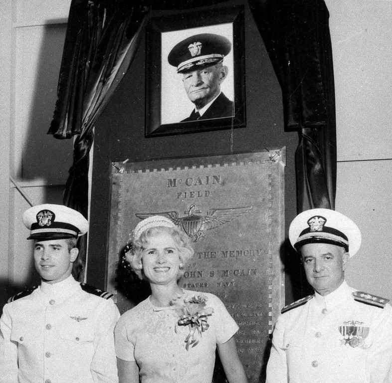. FILE - In this July 14, 1961, file photo, U.S. Navy Lt. John S. McCain III, left, and his parents, Rear Adm. John S. McCain Jr., right, and Roberta Wright McCain stand in front of a plaque with an image of his grandfather, Adm. John S. McCain, as the Naval Air Station Meridian McCain Field is commissioned and named in honor of Adm. McCain in Meridian, Miss. An aide says that U.S. Sen. John McCain died Saturday, Aug. 25, 2018. He was 81. (AP Photo/File)