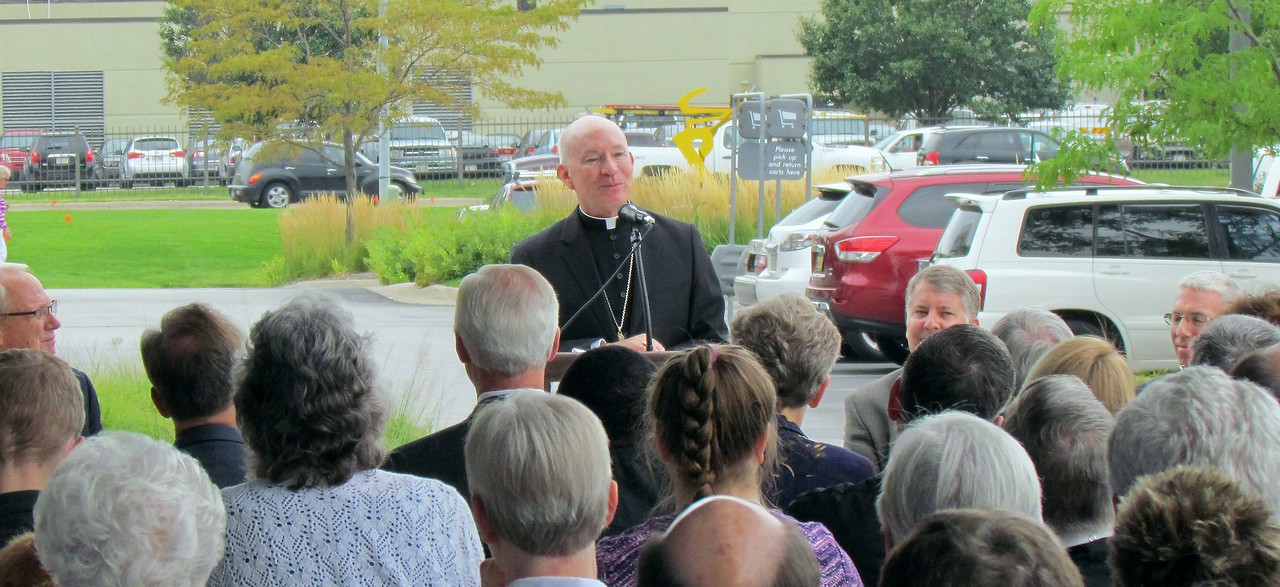 Archbishop George Lucas addresses the attendees of Monday's JPII Newman Center ribbon cutting ceremony.