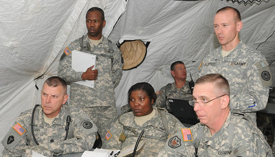 In this image, released by Joint Task Force 71, brigade Soldier of the day SPC Natasha Burkley sits with the JTF-71 commander and command sergeant major to receive the evening's Commander's Update Brief during annual training at Camp Swift. SPC Burkley earned this distinction for exceptional service in identifying a safety hazard and taking immediate steps to correct the fault.