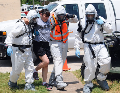 Soldiers from 436th Chemical Company and the 236th Military Police Company assist a casualty while conducting a collective training exercise at the Govalle Water Treatment Facility in Austin, Texas, April 26-27, 2012. This exercise helps Joint Task Force 71 maintain readiness to conduct the Homeland Response Force mission throughout FEMA Region 6.