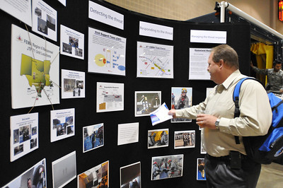 In this image released by the Texas Military Forces, Kelly Cook, homeland security coordinator for the TCEQ examines a display explaining what Joint Task Force 71 is and does during the 2011 Texas Division of Emergency Management Conference, Thursday, April 28, 2011, in San Antonio Texas. The task force is charged with providing defense support to agencies during disasters and other emergencies.  The conference provides the perfect opportunity for task force members to meet and interact with key leaders and organization leaders in a non-emergency setting. (Photo/100th Mobile Public Affairs Detachment, Army National Guard Staff Sgt. Melissa Bright)