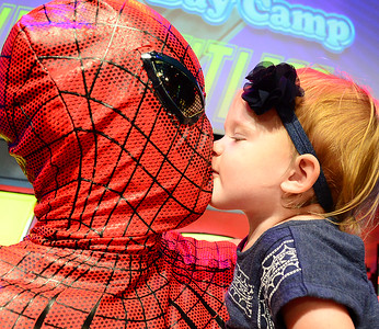 Kevin Harvison | Staff photo Harmony Meeks gives Spider Man, a.k.a. Chris Meeks, a kiss after his daughter Harmony Meeks found out costumed hero goes by another name, Daddy. Meeks and several other vounteers dresses up recently during a Summer Day Camp.