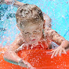 Kevin Harvison | Staff photo<br /> Swayzi Gooding closes her eyes as she makes her way down a Slip and Slide while haveing fun in the sun.