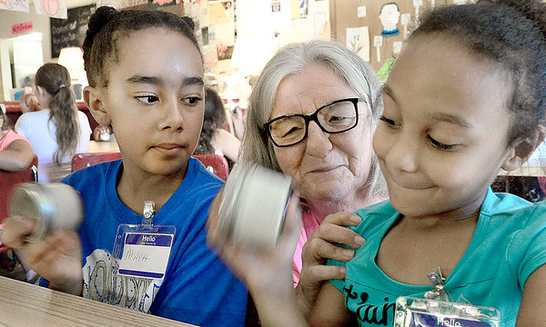 Kevin Harvison | Staff photo The Grand Avenue Community Center Summer Program 2017 is under way from 7 a.m. until 3 p.m. Maya Thornton, left and Aaliyah Batts shake a jar to make home made butter under the watch of OSU Extension Office representative Delois Crone.