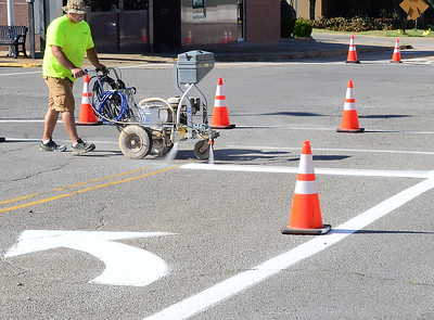 Kevin Harvison | Staff photo McAlester city employee Jeremy Lewis paints the intersection of Third Street and Choctaw Avenue.