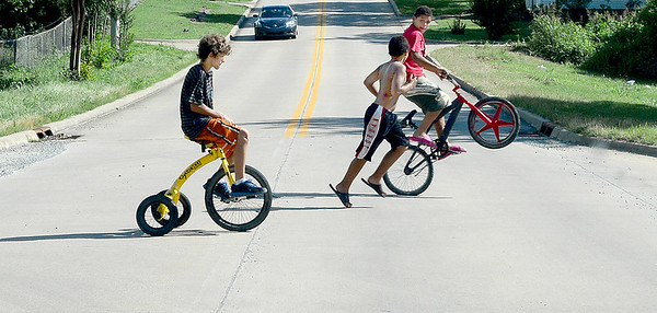 Kevin Harvison | Staff photo<br /> Three kids cross hurry across Second Street in three diffrent modes of transportation.