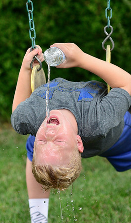 KEVIN HARVISON | Staff photo<br /> Brodie Eddy kicks back to cool off while relaxing on a swing.