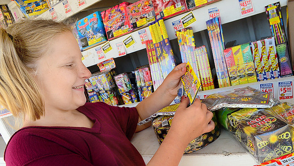 Kevin Harvison | Staff photo<br /> Jovie Runyon looks over some personal fireworks Monday, before the official fireworks day on Wednesday July 4.