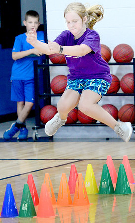 KEVIN HARVISON | Staff photo<br /> Ember Duffey jumps over cones during an agility drill at the Panther Pride summer camp in PIttsburg.