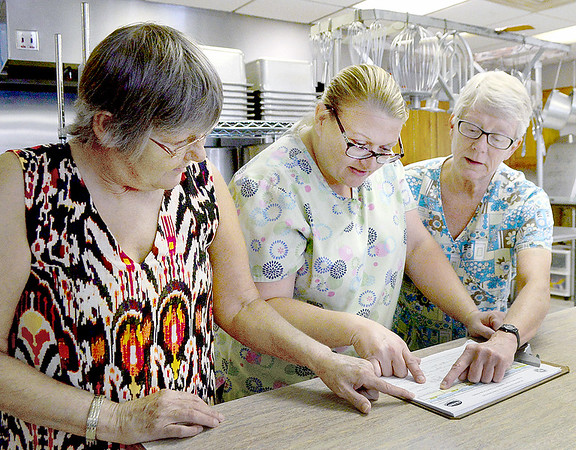 KEVIN HARVISON | Staff photo<br /> Pictured from left, Dottie Anderson, Kara James and Wendy James look over a menu for the upcoming days at the Hartshorne Community Center.
