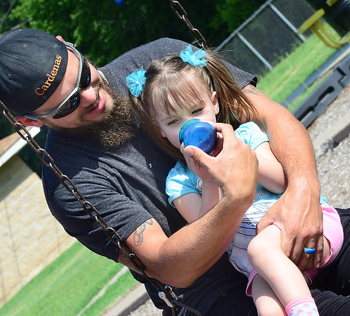 KEVIN HARVISON | Staff photo<br /> Jade Cardenas enjoys some time at Chadick Park with his daughter Sandy Cardenas as the two take a break from playing and rest on a swing.