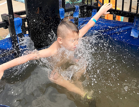 KEVIN HARVISON | Staff photo<br /> Axton Kennon crashes to the water in the dunk tank at the Splash Bash downtown on Choctaw Avenue Saturday. Look for more photos of the Splash Bash in an upcoming Accent page in a Saturday edition of the MNC.