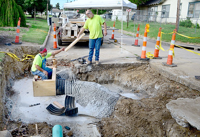 KEVIN HARVISON | Staff photo A McAlester City Crew works on a Form to concrete a storm water drainage box at the corner of Chadick Avenue and Fifth Street. The section of road is scheduled to be open by end of next week if all goes to plan.