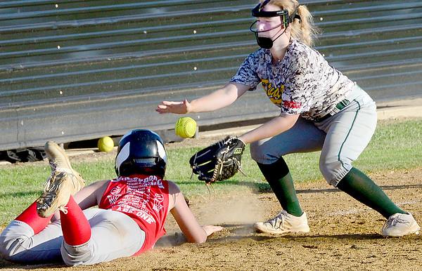 KEVIN HARVISON | Staff photo<br /> A Stuart High School third baseman attempts to make a play on a Whitesborro base runner during a Kiowa Summer League game.