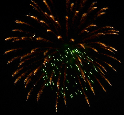 KEVIN HARVISON |<br /> The Waning Crescent Moon appears through a fireworks burst in the sky west of Mcalester Thursday.