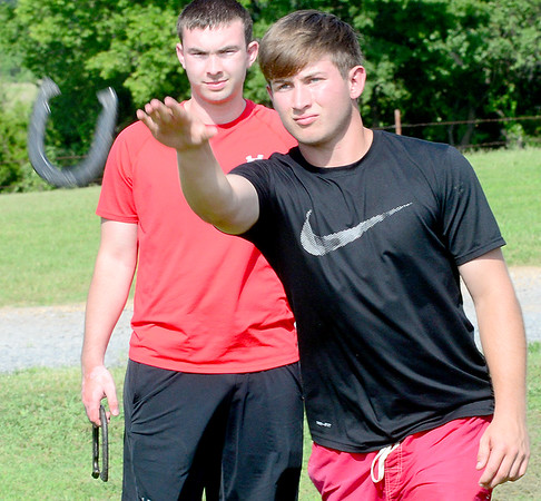 KEVIN HARVISON |<br /> Jake McRay, left waits his turn as Caden Hull, right, pitches a horse shoe during a friendly July game.