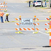 Kevin Harvison | Staff photo<br /> Men work on closing 5th Street from crossing Carl Albert Parkway. Many of the north and south bount roads will not be crossing Carl Albert Parkway.