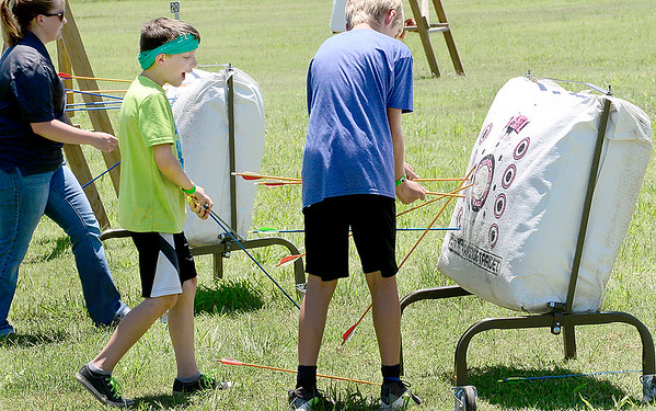 Kevin Harvison | Staff photo<br /> Spencer Czapansky, center, retreaves his arrows archery lessons at the H.E.R.O. Part II Summer Day Camp sponsored by the Kings House Church in McAlester.