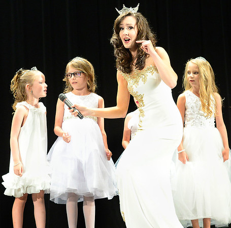 Kevin Harvison | Staff photo<br /> 2017 Miss McAlester Kyleeann Parker holds the microphone for a Little Star contestant Delaney Suter during a performance at the 2018 Miss McAlester Scholarship Pageant contest at S. Arch Thompson Auditorium Saturday.