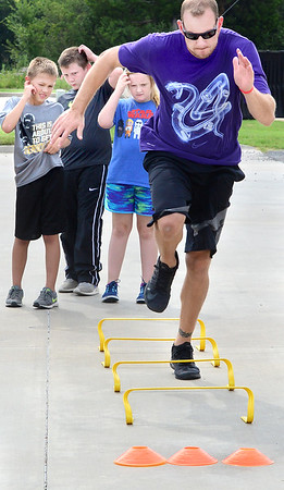 Kevin Harvison | Staff photo<br /> Certified Strength Coach Chris Hearod show kids from the Signature Fitness Summer Camp how to complete and agility obsticle course as the kid study his movement.