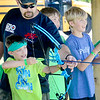 Kevin Harvison | Staff photo<br /> Spencer Czapansky, bottom left, prepares to fire as H.E.R.O. Part II Summer Day Camp volunteer Rob Zummer, above left, helps instruct while campers useing the city archery range west of McAlester on U.S. 270. The day camp is sponsored by the Kings House Church in McAlester.