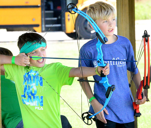 Kevin Harvison | Staff photo<br /> Spencer Czapansky, left, prepares to fire his arrow during H.E.R.O. Part II Summer Day Camp sponsored by the Kings House Church in McAlester.