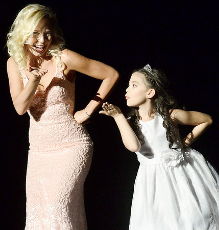 Kevin Harvison | Staff photo<br /> 2018 Miss McAlester contestant, Emerielle Sherman, left, with her Little Star Pazlye Coronel blow a kiss to the audience at the Miss McAlester Scholarship Pageant Saturday at S. Arch Thompson Auditorium.