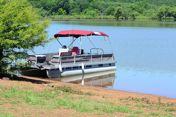 Kevin Harvison   Staff photo<br /> A pontoon boat is tied to a tree on the shore of Lake Eufuala.