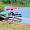 Kevin Harvison | Staff photo<br /> A pontoon boat is tied to a tree on the shore of Lake Eufuala.