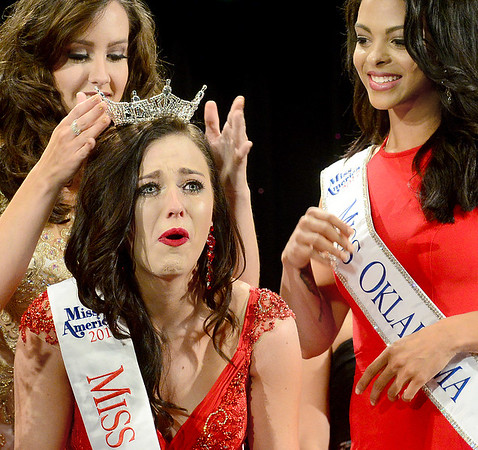 Kevin Harvison | Staff photo<br /> Center, Alexandria Williams, gets crowned the new Miss McAlester 2018 by reigning 2017 Miss McAlester, Kyleeann Parker, left as the current Miss Oklahoma Triana Browne, right, looks on during the 2018 Miss McAlester Scholarship Pageant held Saturday at the S. Arch Thompson Auditorium.