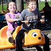 Kevin Harvison | Staff photo<br /> Pictured from left, Maylynn Henry enjoys the ride as Brian Johnson handles the bumble bee spring toy at Chadick Park.