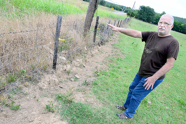 Kevin Harvison | Staff photo Ernest Edwards at 355 State Highway 113 shows where water is washing away the bottom of his fence due to what he believes is ditch negligence.