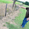 Kevin Harvison | Staff photo<br /> Ernest Edwards at 355 State Highway 113 shows where water is washing away the bottom of his fence due to what he believes is ditch negligence.