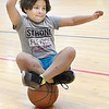 Kevin Harvison | Staff photo<br /> Hiedi Bryan attempts to balance on top of a basketball while taking a break from shooting around inside the McAlester Boys and Girls Club.