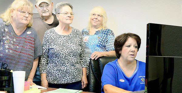 Kevin Harvison | Staff photo<br /> Pictured from left, Carla Morris, voters Albert Rose and his wife Donna Rose, Kathy and Tonya Barnes work to process and early voter for the election.