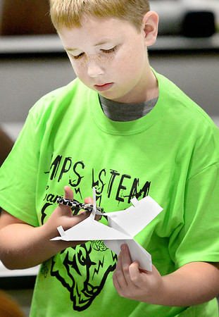 Kevin Harvison | Staff photo<br /> McAlester Public Schools  STEM Camp student Cole Johnson, concentrates on the fine tuning of his paper air plane before a distance competition.