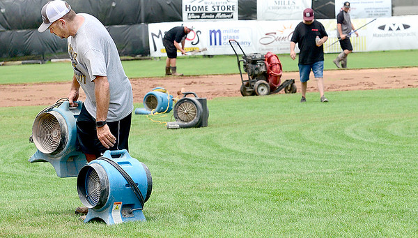 KEVIN HARVISON | Staff photo<br /> Work continues on Mike Deak Field Friday afternoon to prepare for play of the Junior Sunbelt Classic from massive amounts of rain in the area recently.