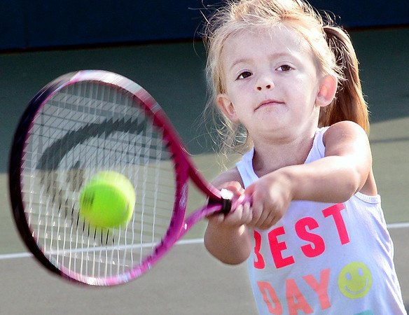 KEVIN HARVISON | Staff photo<br /> Violet Walters powers a ball over the net during her morning lessons from the City Summer Tennis Camp Tuesday at Chadick Park.