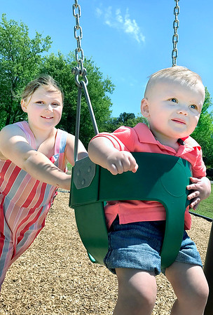 KEVIN HARVISON | Staff photo<br /> Pictured from left, Presley Gleese pushes Dawson Patterson as the two test out the new playground equipment at Stuart's City Park.