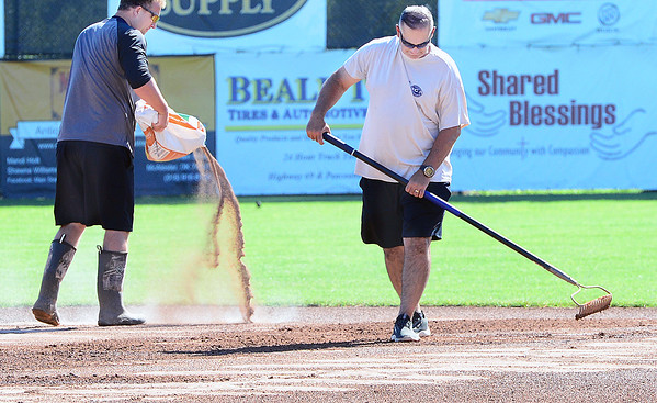 KEVIN HARVISON |<br /> AJ Mason, left and Kevin Harmon, right, work to get Mike Deak Field into playing condition Wednesday morning for the Junior Sunbelt Classic in McAlester.