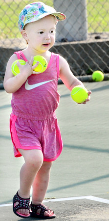 KEVIN HARVISON | Staff photo<br /> Ella Walters helps gather tennis balls during the City Summer Tennis Camp at Chadick Park.